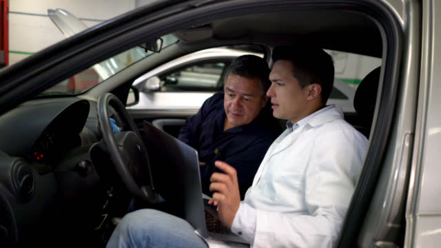 Mechanic and specialist checking a car's computer using a laptop