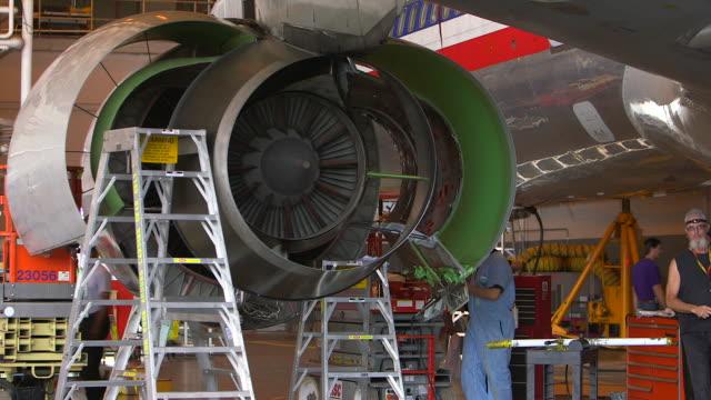 stockvideo's en b-roll-footage met mechanic ascends ladder to work inside jet engine of jetliner in hanger/dfw international airport, dallas-fort worth, texas, usa - keukentrap