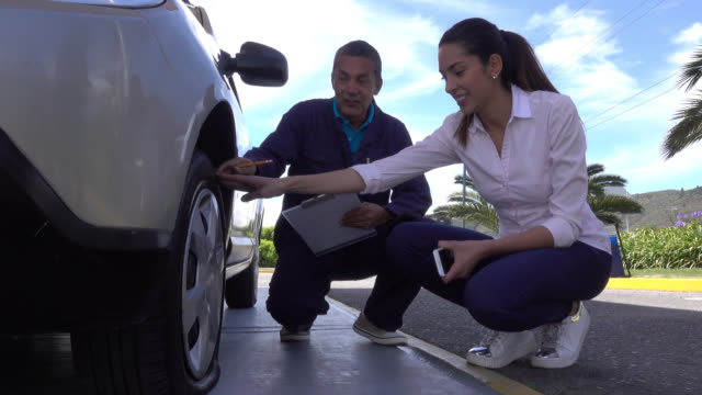 mechanic assistance arriving to help a woman with a flat tire - vehicle breakdown stock videos and b-roll footage