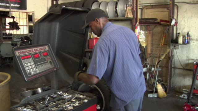 MS ZI ZO PAN Mechanic balances tire in machine / Los Angeles, California, USA
