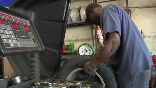 MS Mechanic balances tire in machine / Los Angeles, California, USA