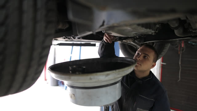 mechanic changes engine oil in auto repair shop - motor oil stock videos & royalty-free footage