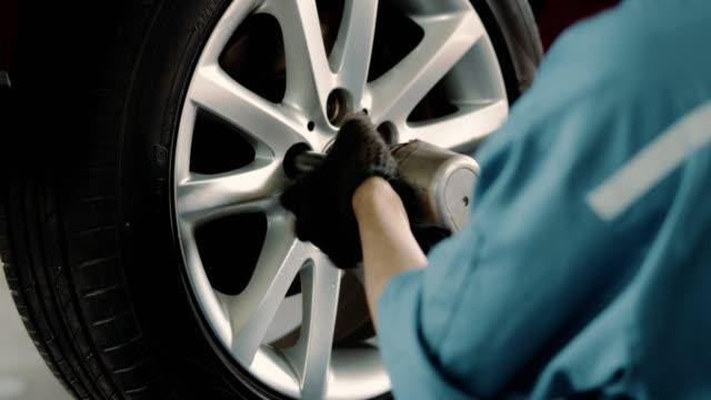 vídeos y material grabado en eventos de stock de mecánico cambiando el neumático en el taller de reparación automática - neumatico