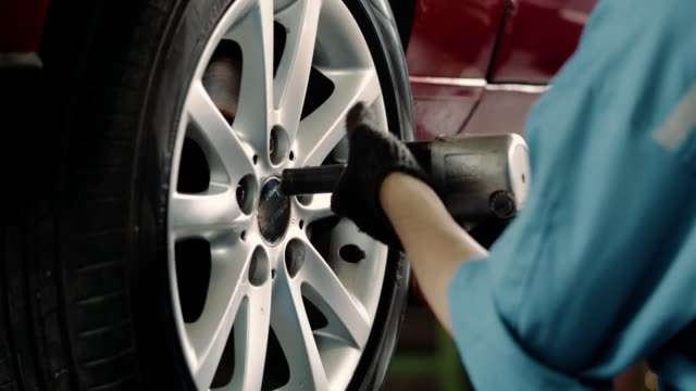 vídeos y material grabado en eventos de stock de mecánico cambiando el neumático en el taller de reparación automática - mecánico de coches