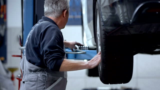 stockvideo's en b-roll-footage met mechanic changing the tire - autoband