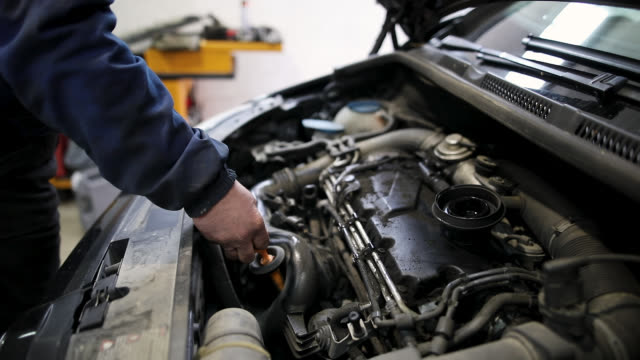 mechanic checking oil level in the engine in auto repair shop - motor oil stock videos & royalty-free footage