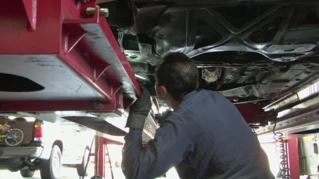 ms mechanic checking under car with light / los angeles, california, usa - 中年の男性だけ点の映像素材/bロール