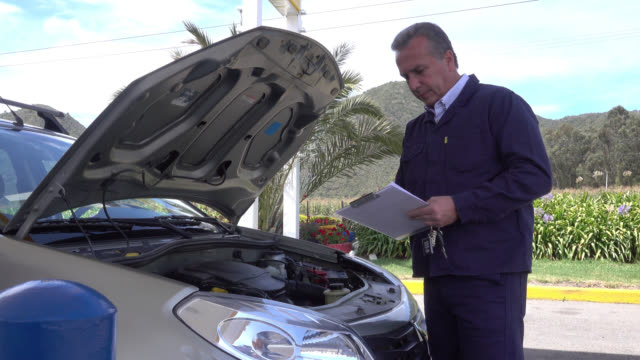 Mechanic doing a check list of the repairs made on car