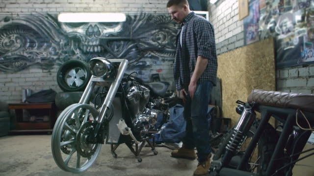 Mechanic examining an unfinished motorcycle