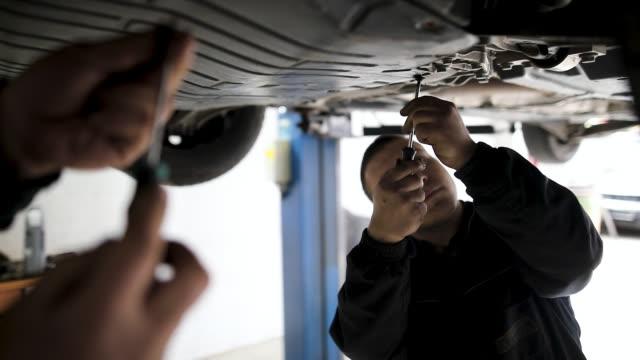 vídeos y material grabado en eventos de stock de mecánico examinando el tren de rodaje en auto repair shop - debajo de