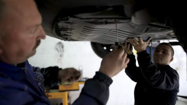 mechanic examining undercarriage at auto repair shop - mechanic stock videos & royalty-free footage