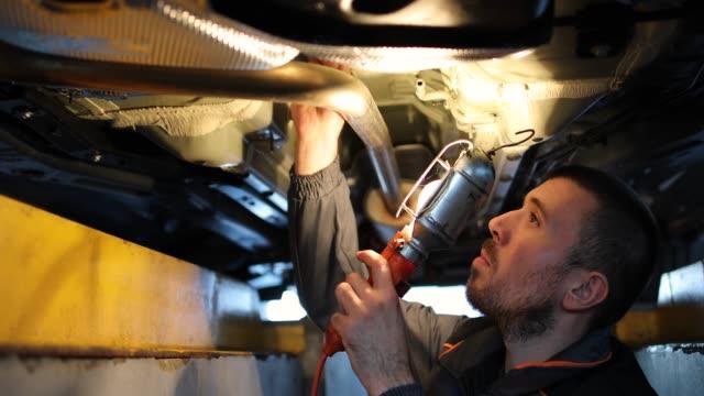 vídeos y material grabado en eventos de stock de mecánico examinando la parte inferior del coche - mecánico de coches