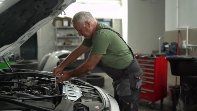 自動車修理工場で車両フードを調べるメカニック - 自動車部品点の映像素材/bロール