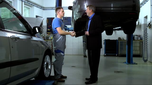 vídeos de stock e filmes b-roll de mecânico explicando a reparação de cliente - cliente