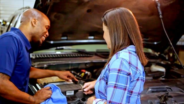 Mechaniker, erklärt, dass Kunden in Autowerkstatt Reparaturen am Fahrzeug.