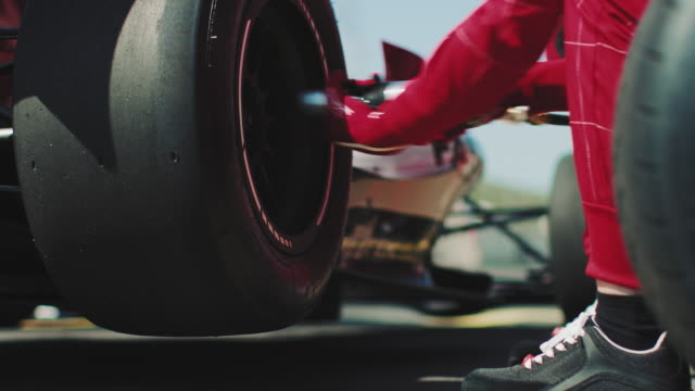Mechanic fastening tire of racecar at pit stop