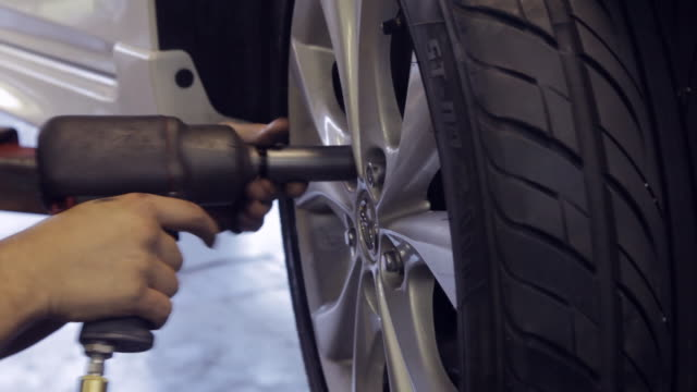 mechanic fastening wheel with screwdriver drill - tyre stock videos & royalty-free footage