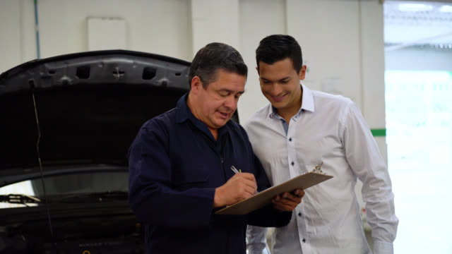 vídeos de stock e filmes b-roll de mechanic going over a list of the things fixed of the car to a customer - prancheta