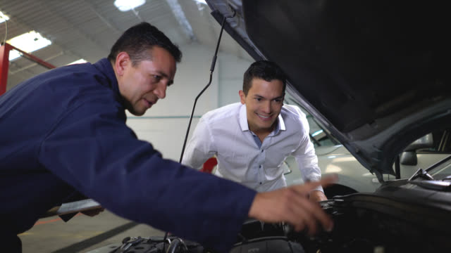 Mechanic holding a clipboard and showing a customer what he fixed of the car engine