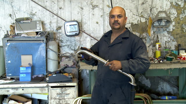 A mechanic holds a pipe in a garage.