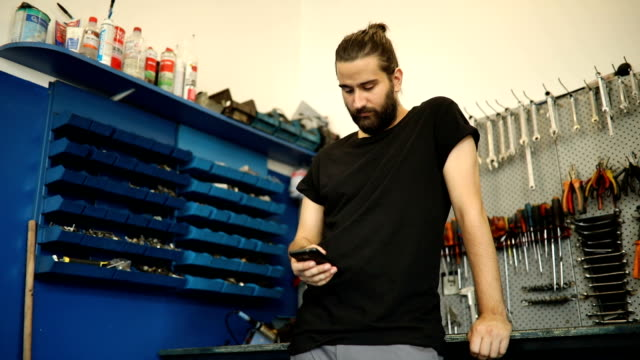 mechanic in garage texting - long hair stock videos and b-roll footage