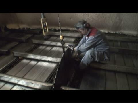 a mechanic installs a saw blade at a paper mill. - 製紙工場点の映像素材/bロール