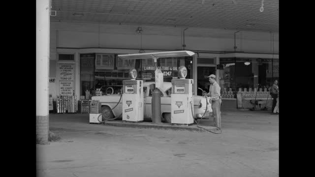 vídeos de stock e filmes b-roll de 1962 a mechanic is interrupted while working on a car - frentista