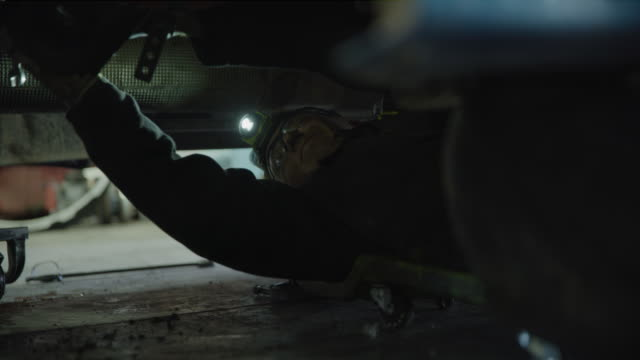 mechanic laying on creeper working underneath truck / aurora, utah, united states - mechanic stock videos & royalty-free footage