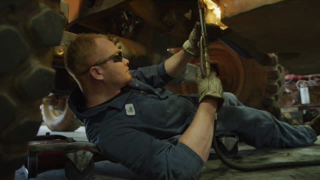 vidéos et rushes de mechanic laying under truck and cutting with torch / aurora, utah, united states - réparer