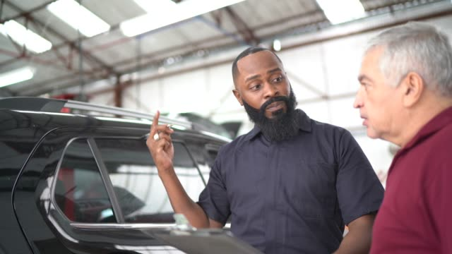 mechanic man explaining to his customer the defect of his car in a repair shop - customer focused stock videos & royalty-free footage