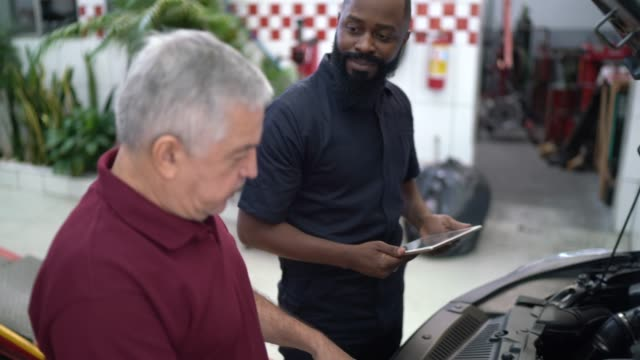 mechanic man explaining to his customer the defect of his car in a repair shop - technician stock videos & royalty-free footage