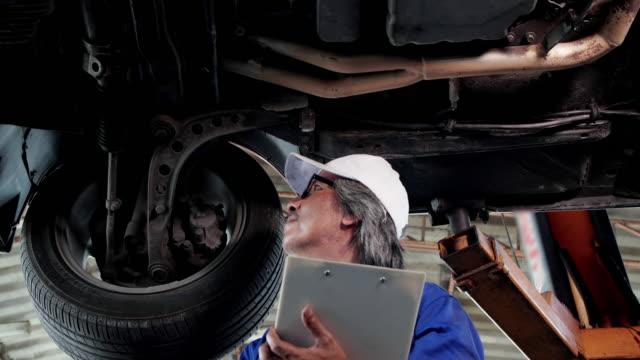 ワーク ショップ車のサービス、修理、保守および人々 のコンセプトで働いていたメカニックの男性。 - 機械工点の映像素材/bロール