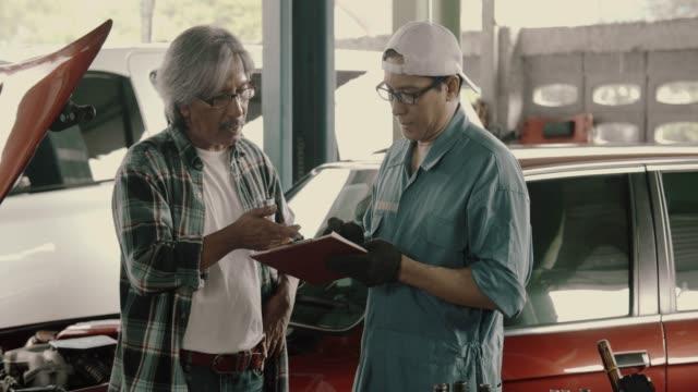 mechanic men and senior men customer checklist car repair - repair shop stock videos & royalty-free footage
