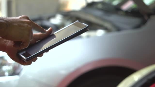 mechanic overhauling a car by tablet - repair garage stock videos & royalty-free footage