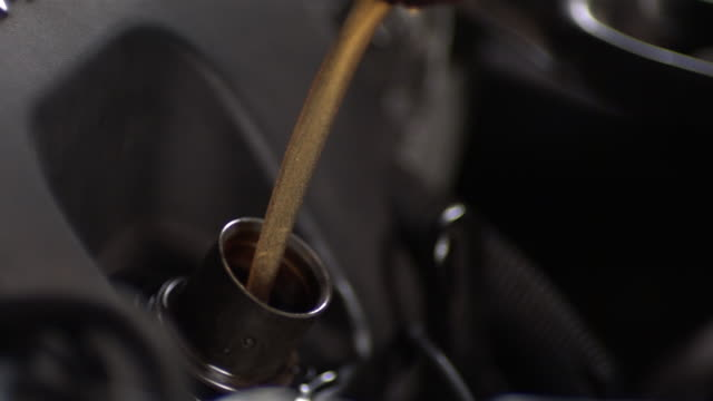stockvideo's en b-roll-footage met cu slo mo mechanic pouring oil into engine / bergenfield, , new jersey, usa    - motor oil