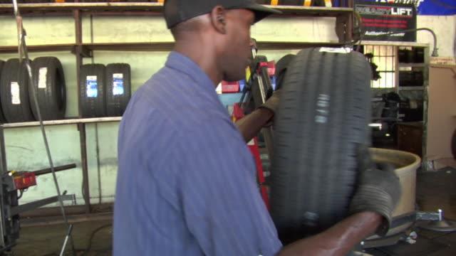 MS Mechanic puts new tire onto wheel / Los Angeles, California, USA