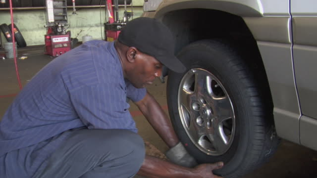 ms mechanic putting new tire on car / los angeles, california, usa - 中年の男性だけ点の映像素材/bロール