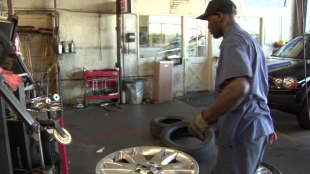 ms mechanic removing tire from wheel with machine / los angeles, california, usa - 中年の男性だけ点の映像素材/bロール