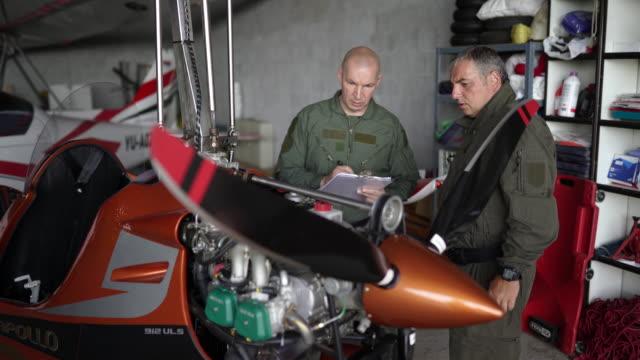 mechaniker repariert flugzeugtriebwerk in einem flughafenhangar - luftfahrzeug stock-videos und b-roll-filmmaterial