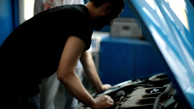 mechanic repairing her car - bonnet stock videos & royalty-free footage