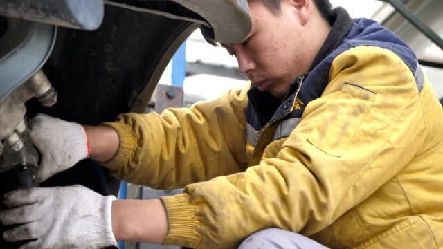 mechanic repairs offroad vehicle in a workshop on oct 22 2017 in beijing china - querfeldeinrennen stock-videos und b-roll-filmmaterial
