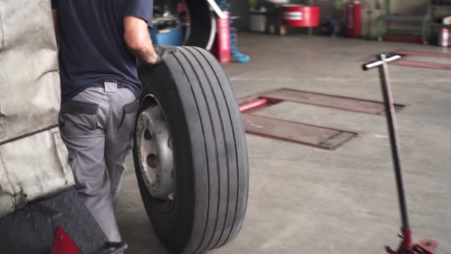 mechanic rolling the tire to another place - tyre stock videos & royalty-free footage
