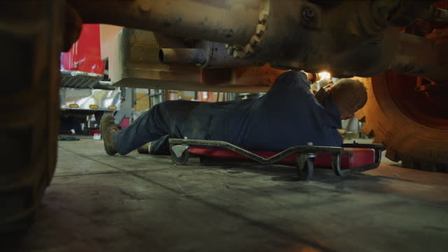 mechanic rolling under truck and cutting with torch / aurora, utah, united states - verkstad bildbanksvideor och videomaterial från bakom kulisserna
