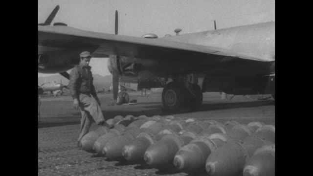 us mechanic rolls bomb into place among rows of bombs on tarmac next to bomber / two mechanics work on bombs / cu man preparing bomb / two men... - bomber plane stock videos and b-roll footage