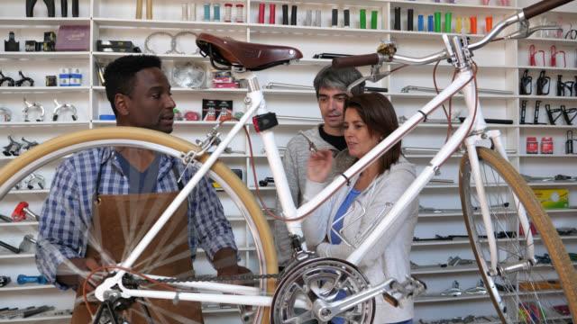 vídeos de stock, filmes e b-roll de mecânico, mostrando um casal que deixou sua bicicleta de manutenção que está funcionando perfeitamente - consertando