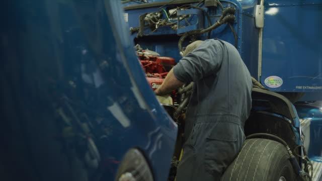 vidéos et rushes de mechanic standing and repairing engine of blue truck / aurora, utah, united states - réparer