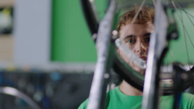 mechanic takes bicycle wheel, places it on truing stand, and spins in bike repair shop - calliper stock videos and b-roll footage