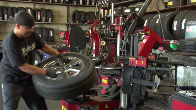 stockvideo's en b-roll-footage met ms mechanic takes the tire off machine / los angeles, california, usa - part of a series