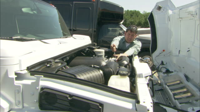 a mechanic uses a wrench on a vehicle and closes the hood. - pick up truck stock videos and b-roll footage