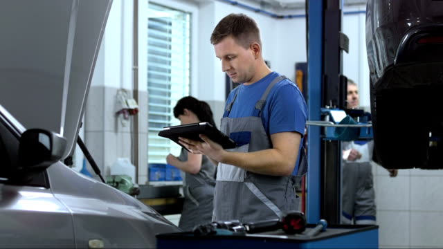 stockvideo's en b-roll-footage met mechanic using a digital tablet - automobile industry
